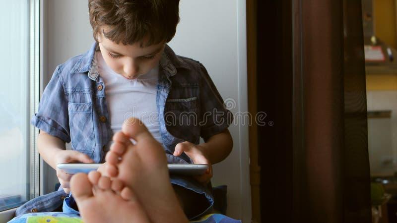 RETRATO: El niño pequeño lindo se sienta en un alféizar en casa y toca una tableta fotografía de archivo libre de regalías
