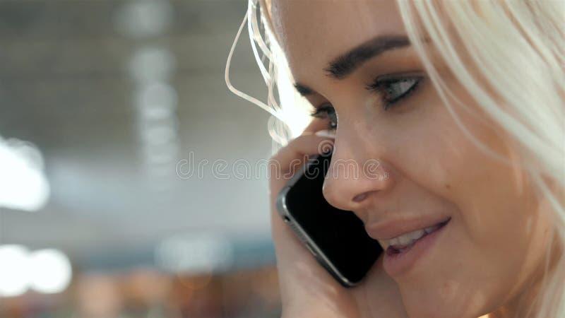 Retrato elegante de hablar rubio joven hermoso en el teléfono en el fondo de la calle que sonríe y que presenta en imagen de archivo