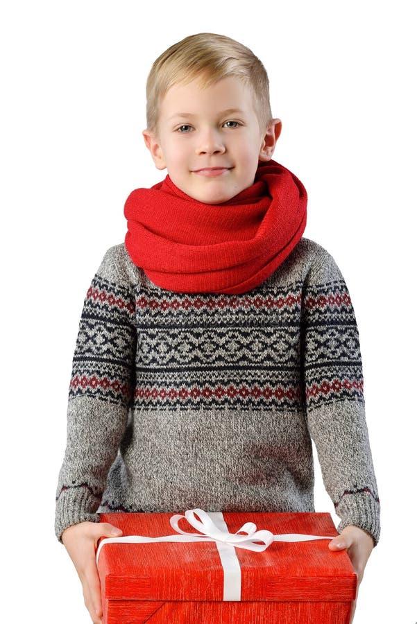 Retrato elegante de um menino adorável da criança na camiseta morna do inverno e no lenço vermelho no fundo branco com caixa atua fotografia de stock royalty free