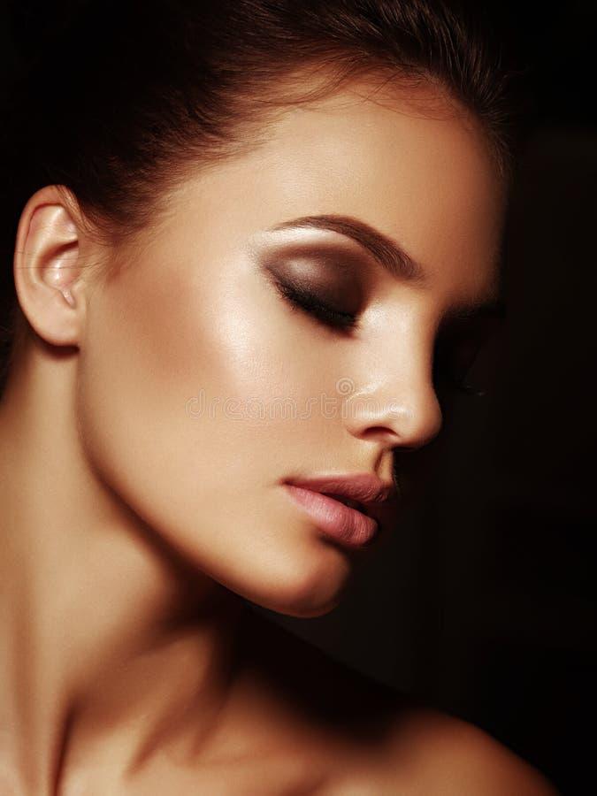 Retrato elegante de una morenita desnuda atractiva atractiva con los labios llenos y los ojos cerrados en el fondo negro foto de archivo