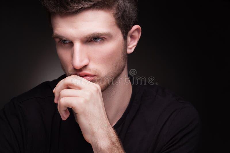 Retrato elegante del hombre joven en negro imagenes de archivo