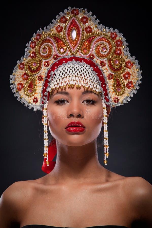 Retrato elegante do close up de uma mulher afro-americano bonita com o kokoshnik ricamente decorado em sua cabeça Estilo do russo foto de stock