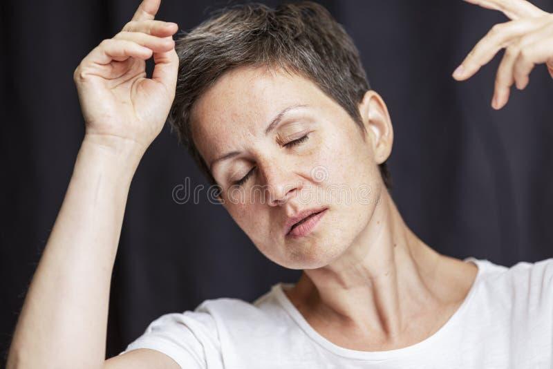Retrato emocional de uma mulher adulta com cabelo curto e os olhos fechados Close-up Fundo preto imagens de stock royalty free