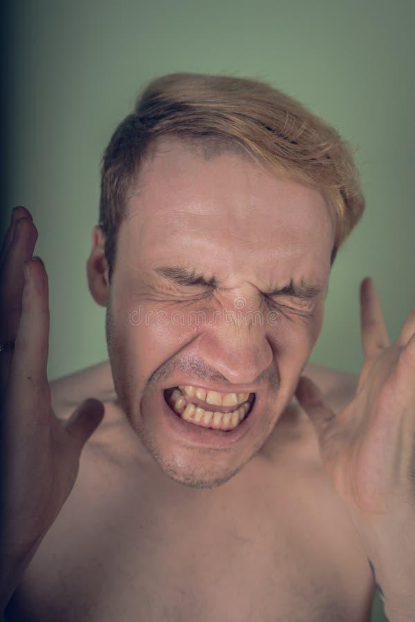 Retrato emocional de un individuo loco en primer concepto: el ataque de nervios, la enfermedad mental, los dolores de cabeza y la fotografía de archivo