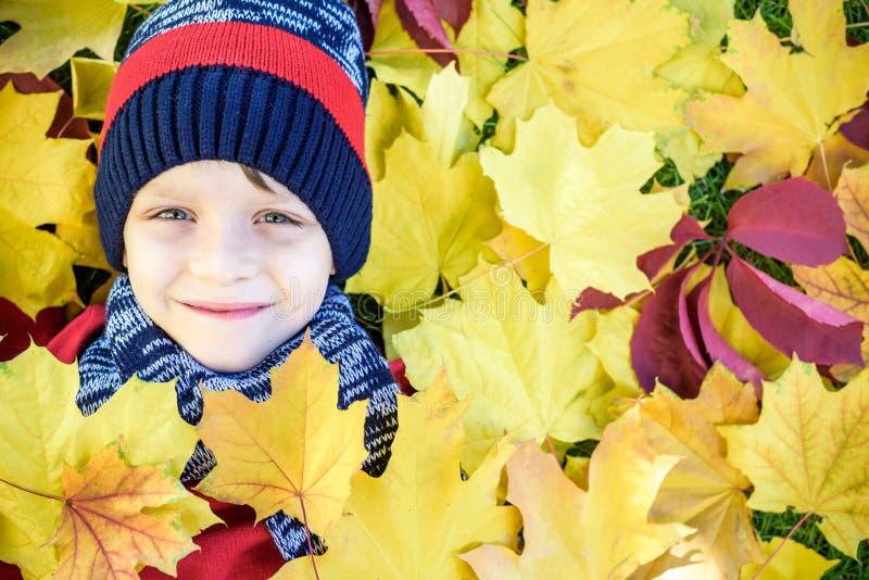 Retrato emocional de un niño pequeño feliz y activo que mira la cámara con una sonrisa que miente en la suya detrás en una alfomb fotos de archivo