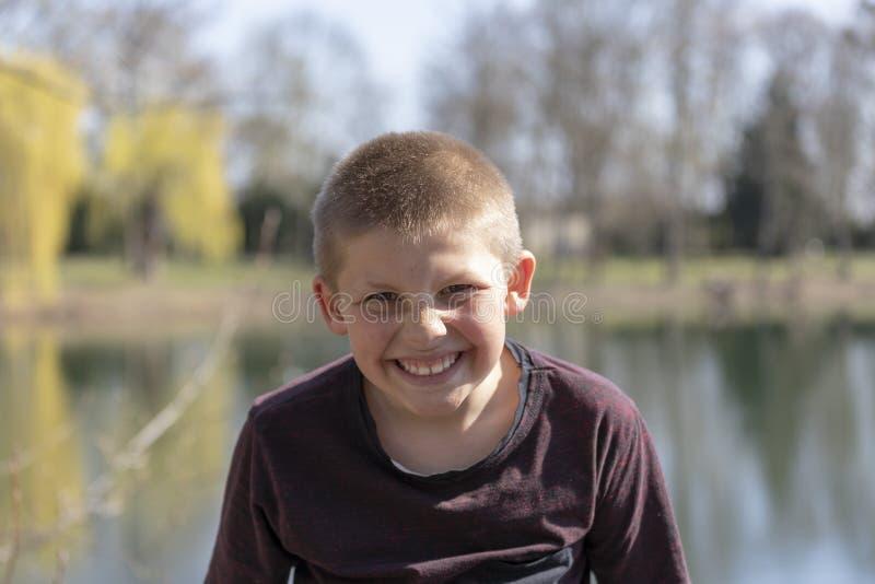 Retrato emocional de una clase y niño pequeño feliz que mira con una sonrisa, lago en el fondo imagenes de archivo