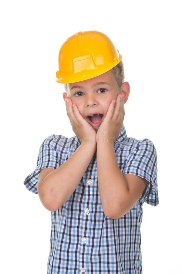 Retrato emocional do busto do menino adolescente caucasiano que veste a camisa azul e o capacete amarelo, isolado no fundo branco fotos de stock