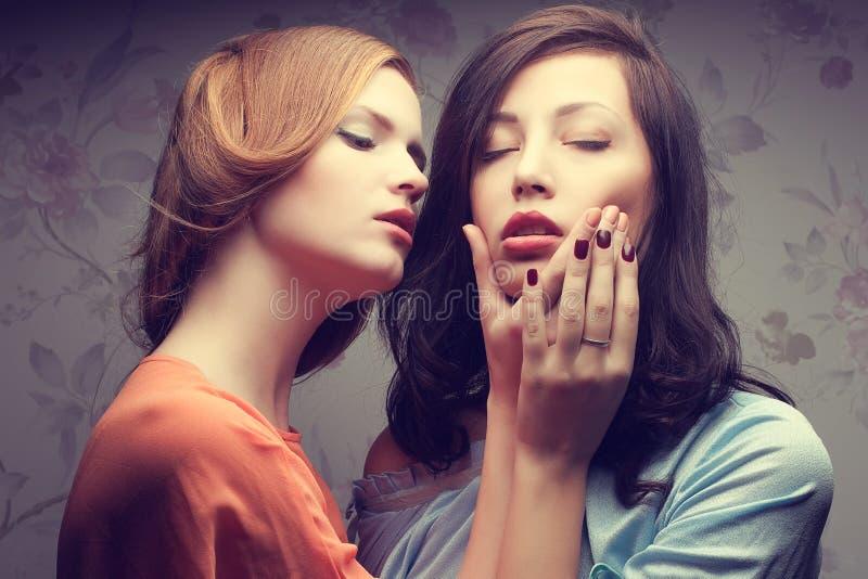 Retrato emotivo de duas amigas lindos em azul e em alaranjado fotografia de stock