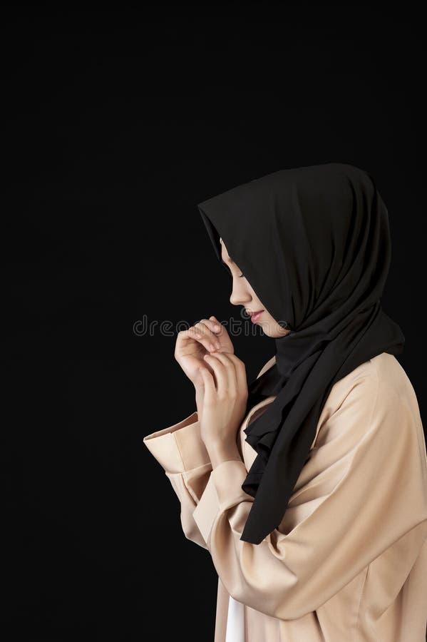 retrato en muchacha musulmán hermosa del perfil en una bufanda negra en su cabeza en un fondo negro foto de archivo libre de regalías