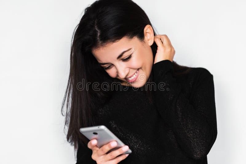 Retrato en perfil de la mujer feliz joven atractiva que usa el teléfono elegante con sonrisa dentuda sana foto de archivo libre de regalías