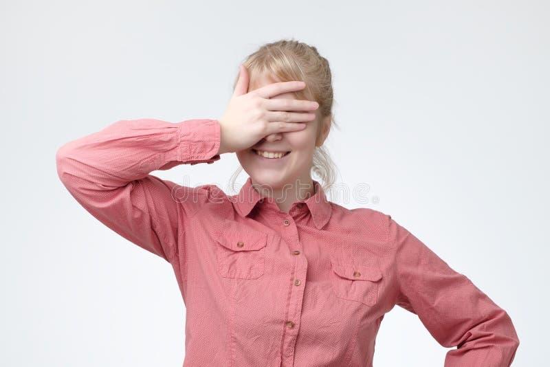Retrato engraçado da menina loura de sorriso para fechar seus olhos com suas mãos, presente de espera fotografia de stock royalty free