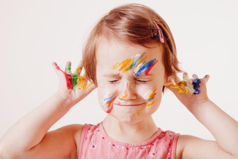 Retrato engraçado das mãos pintadas coloridas e do fac da menina alegre bonito da criança fotografia de stock