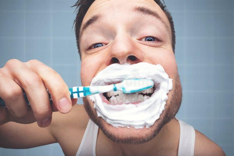 Retrato engraçado de um homem que escova seus dentes com muita espuma fotografia de stock royalty free