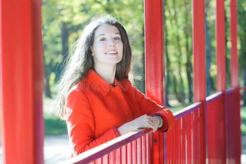 Retrato ensolarado da jovem mulher que veste o revestimento alaranjado no fundo do parque da montanha russa fotos de stock