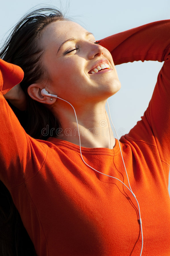 Retrato ensolarado da música de escuta da mulher feliz imagem de stock