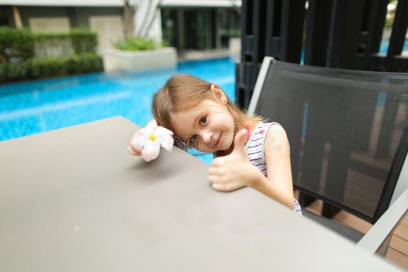 Retrato ensolarado de garotinha mostrando polegares para cima ou algo assim foto de stock royalty free
