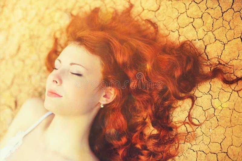 Retrato ensolarado de uma jovem mulher de relaxamento com o cabelo vermelho encaracolado longo chique que encontra-se na terra ra imagem de stock