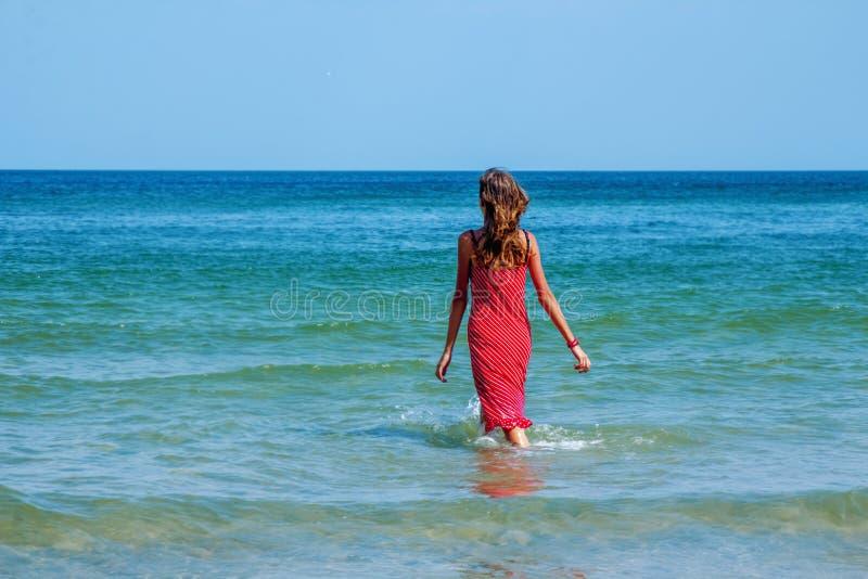 Retrato ensolarado do verão da menina moreno nova bonita feliz que tem o divertimento na praia do mar azul curso, felicidade, res imagem de stock
