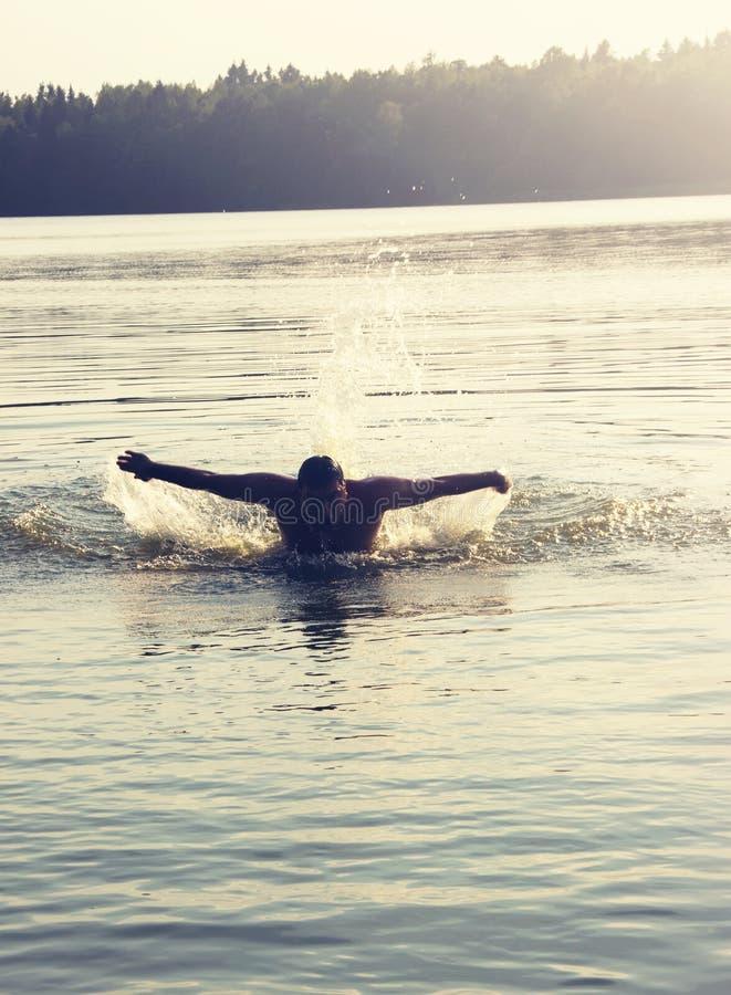 Retrato entonado de la natación del hombre en la puesta del sol imagen de archivo libre de regalías