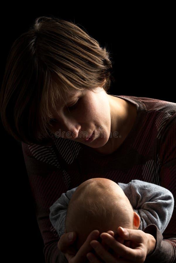 Retrato escuro de uma mãe e de um bebê loving imagens de stock royalty free