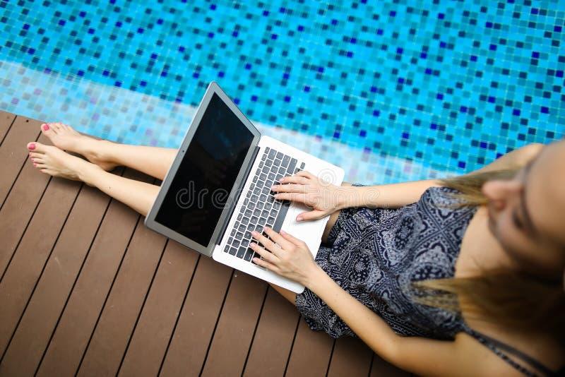 Retrato estreito de uma mulher feliz com o laptop ensolarado no dia em que nadava fotografia de stock royalty free