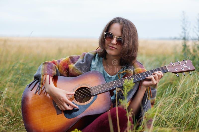 Retrato exterior da fêmea atrativa com os óculos de sol vestindo do cabelo escuro que jogam a guitarra acústica que demonstra seu imagem de stock