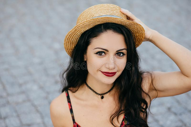 Retrato exterior da fêmea moreno com olhos escuros, bordos vermelhos e chapéu vestindo do verão da pele saudável, mantendo sua mã fotografia de stock