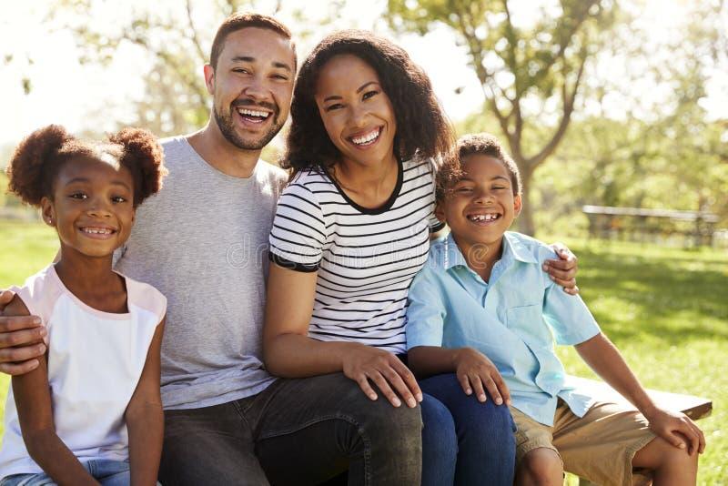 Retrato exterior da família de sorriso que senta-se no banco no parque imagens de stock royalty free