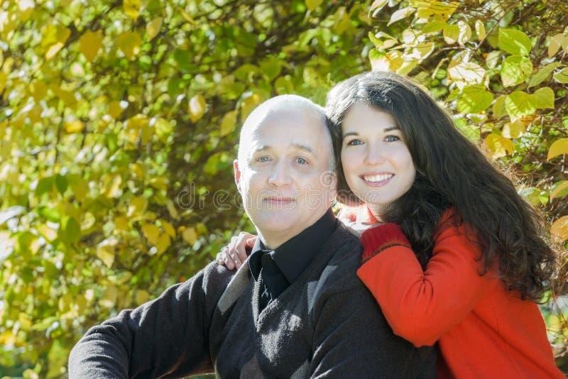 Retrato exterior da família do parque do outono da filha adulta de sorriso que abraça seu pai superior imagens de stock royalty free