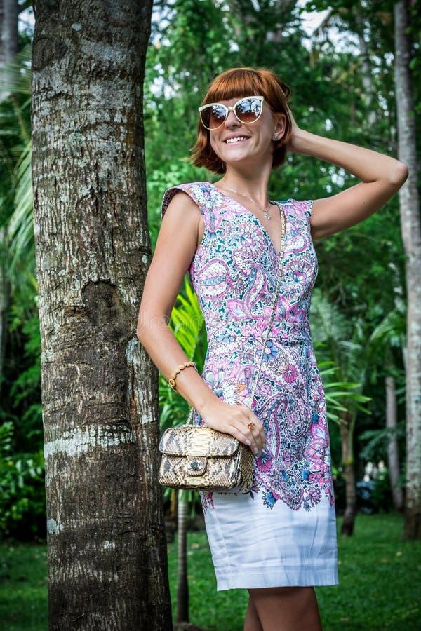 Retrato exterior da forma da senhora à moda nova sensual do encanto nos óculos de sol com o saco feito a mão luxuoso do pitão do  imagens de stock