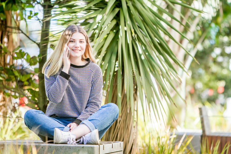 Retrato exterior da menina adolescente de sorriso feliz nova que usa o pho da pilha imagens de stock royalty free