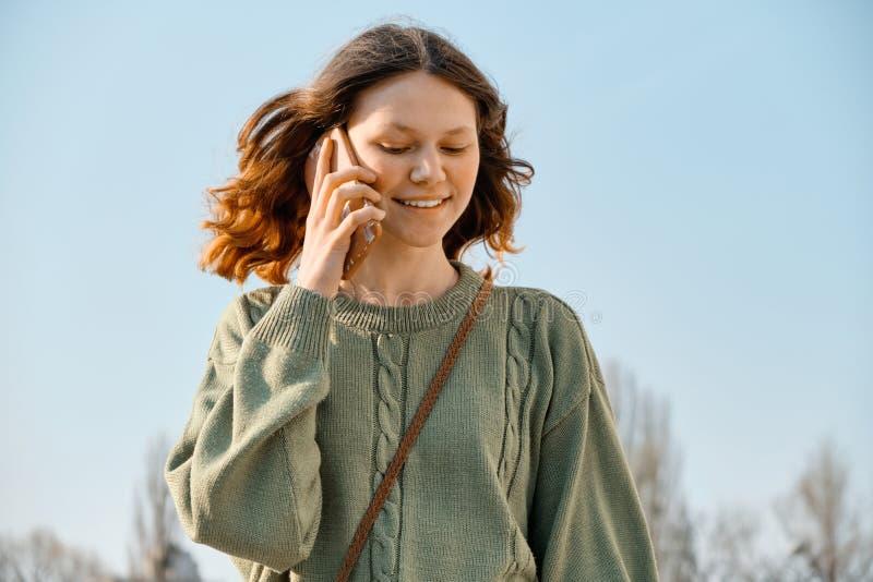 Retrato exterior da menina adolescente de sorriso que anda e que fala no telefone, fundo do céu azul fotografia de stock royalty free