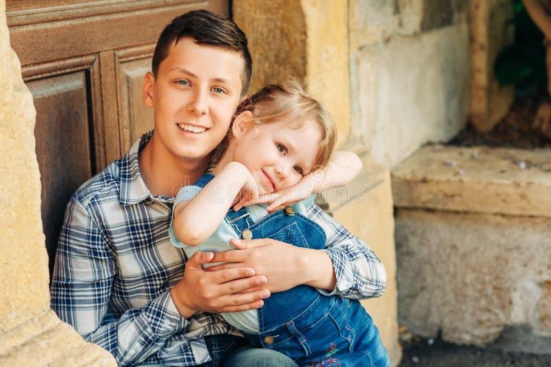 Retrato exterior da menina adorável com irmão adolescente imagens de stock