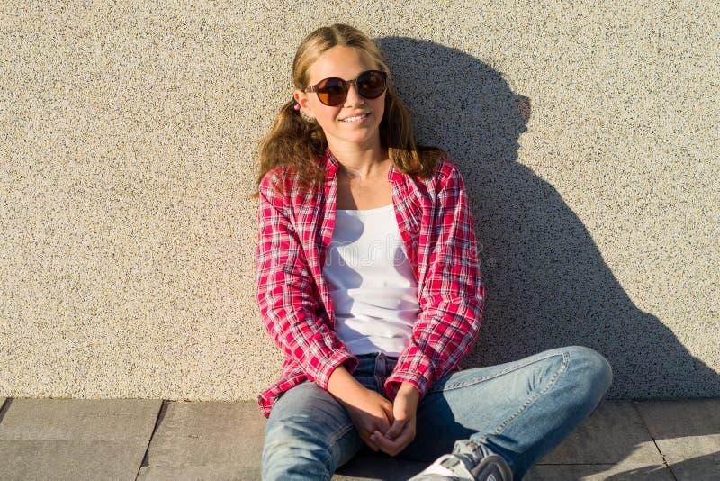 Retrato exterior da menina atrativa nova nos óculos de sol, sorrindo e olhando na câmera, fundo de uma parede cinzenta ensolarada imagem de stock