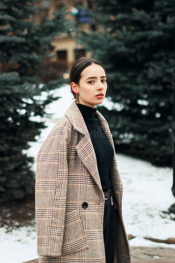 Retrato exterior da menina bonita nova do brunett no revestimento cinzento imagem de stock royalty free