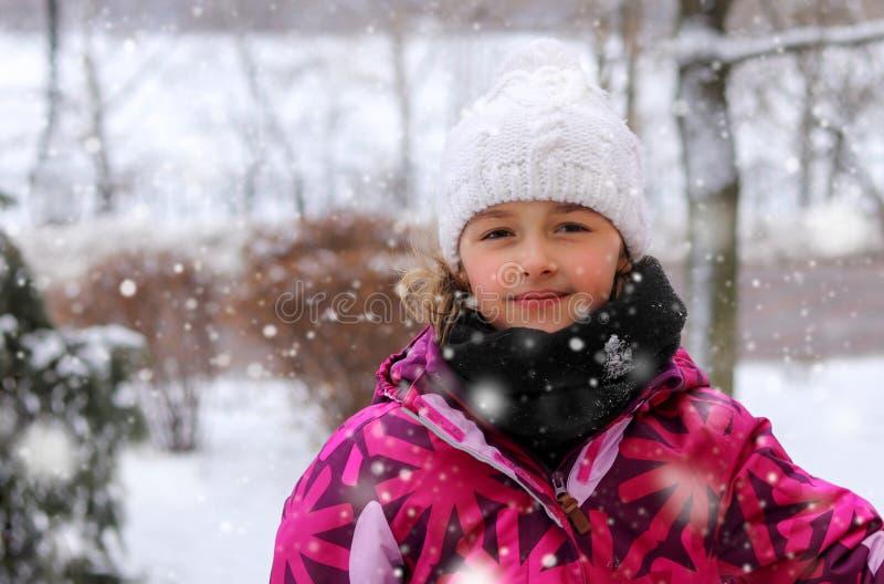 Retrato exterior da menina bonito no chapéu feito malha branco no parque do inverno sob a queda de neve que sorri olhando a câmer fotos de stock