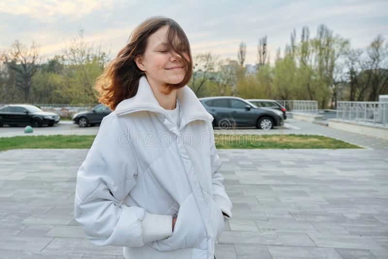 Retrato exterior da menina do adolescente 15 anos velha, menina que sorri com cabelo marrom longo no revestimento branco fotos de stock royalty free