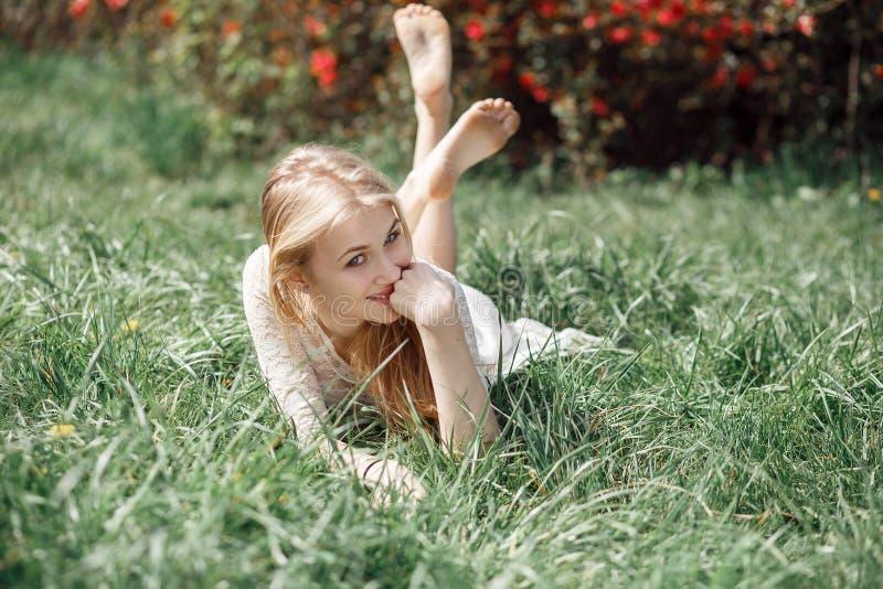 Retrato exterior da menina loura bonita que encontra-se na grama verde imagem de stock