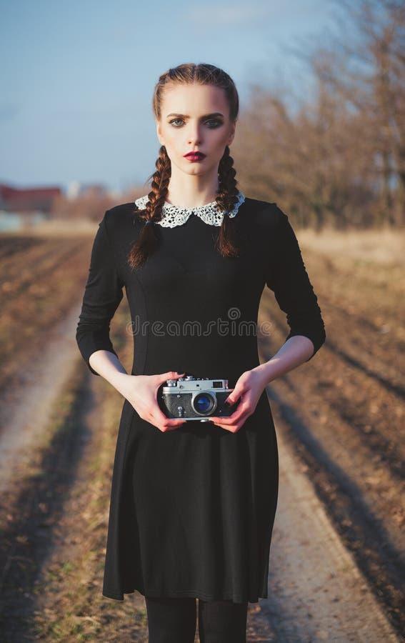 Retrato exterior da moça bonito no vestido preto antiquado com a câmera do filme do vintage nas mãos fotos de stock