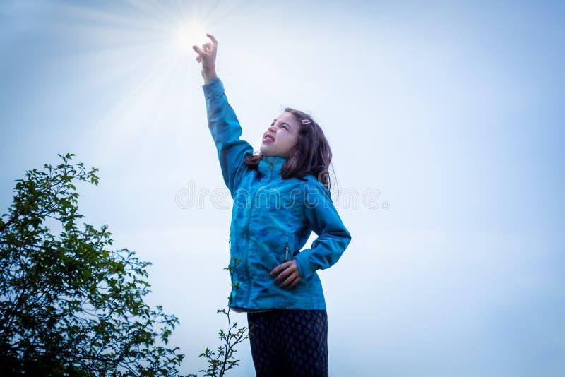 Retrato exterior da moça no casaco azul que alcança seu braço no ar para travar o sol fotos de stock royalty free