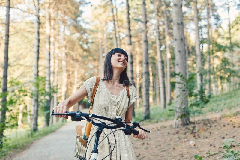 Retrato exterior da morena nova atrativa em um chapéu em uma bicicleta fotografia de stock royalty free