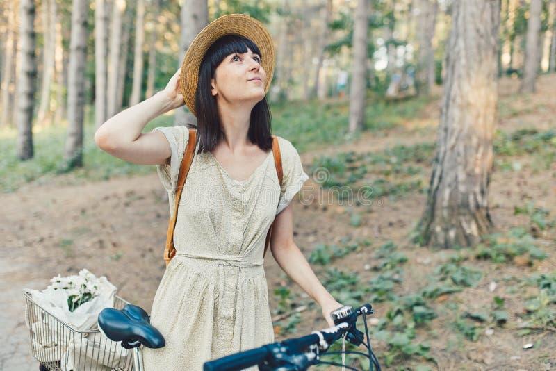 Retrato exterior da morena nova atrativa em um chapéu em uma bicicleta imagem de stock royalty free