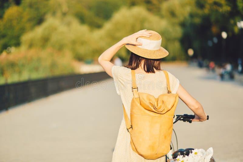 Retrato exterior da morena nova atrativa em um chapéu em uma bicicleta imagens de stock royalty free