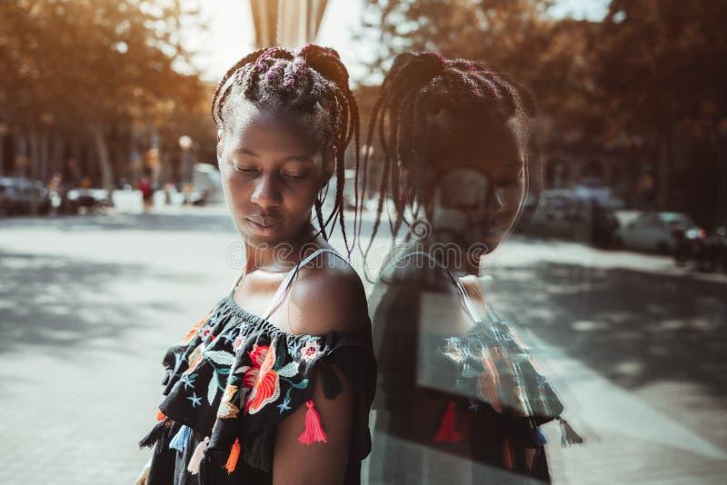 Retrato exterior da mulher afro-americano nova perto de um wa de vidro foto de stock