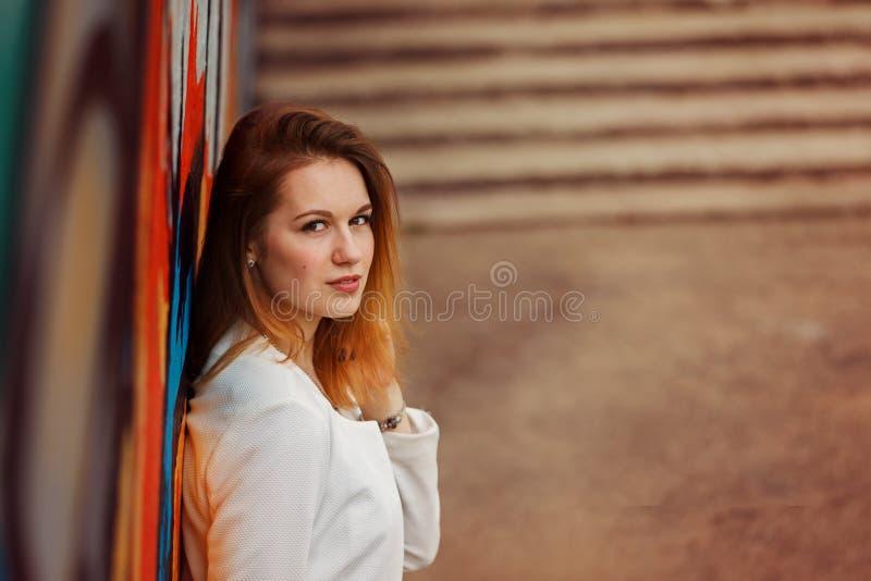 Retrato exterior da mulher bonita nova que levanta na rua No dia ensolarado Fôrma fêmea Estilo de vida da cidade fotos de stock royalty free