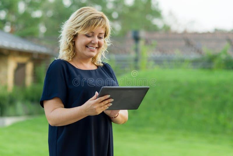 Retrato exterior da mulher de negócio maduro com tabuleta digital, jardim verde do fundo de uma residência privada fotos de stock royalty free