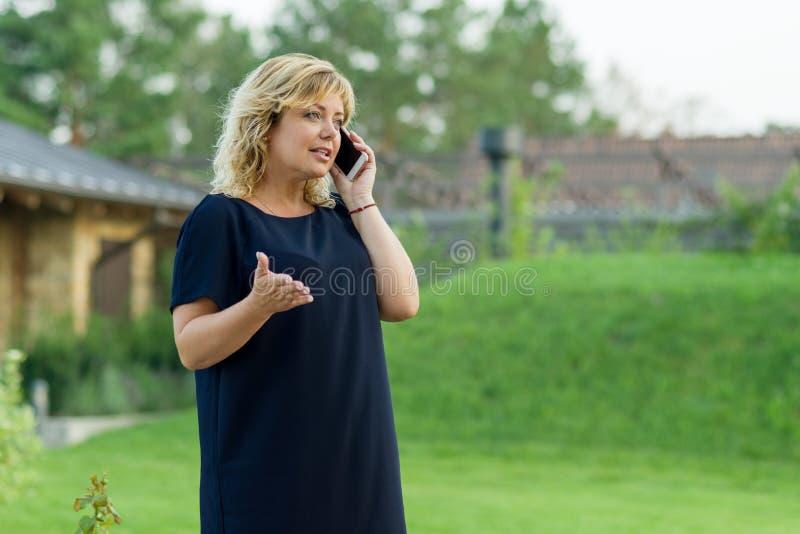 Retrato exterior da mulher de negócio maduro com telefone celular, jardim verde do fundo de uma residência privada imagens de stock