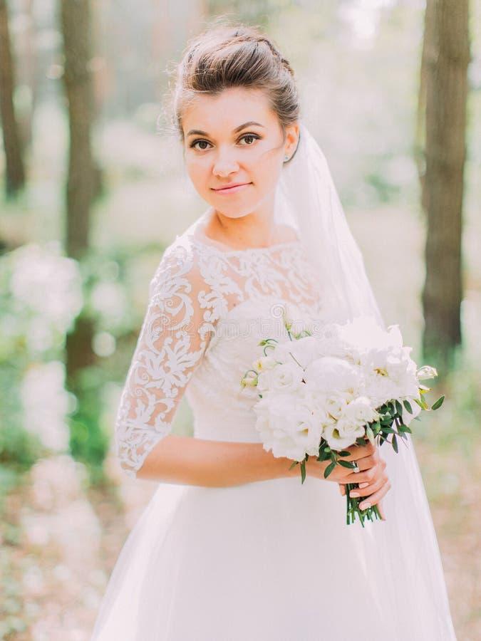 Retrato exterior da noiva encantador que guarda o ramalhete do casamento das peônias fotos de stock