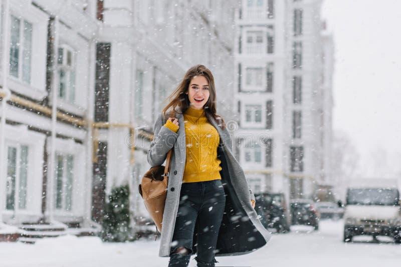 Retrato exterior da senhora espetacular na camiseta amarela que anda abaixo da rua no dia de inverno morno Foto de satisfeito foto de stock