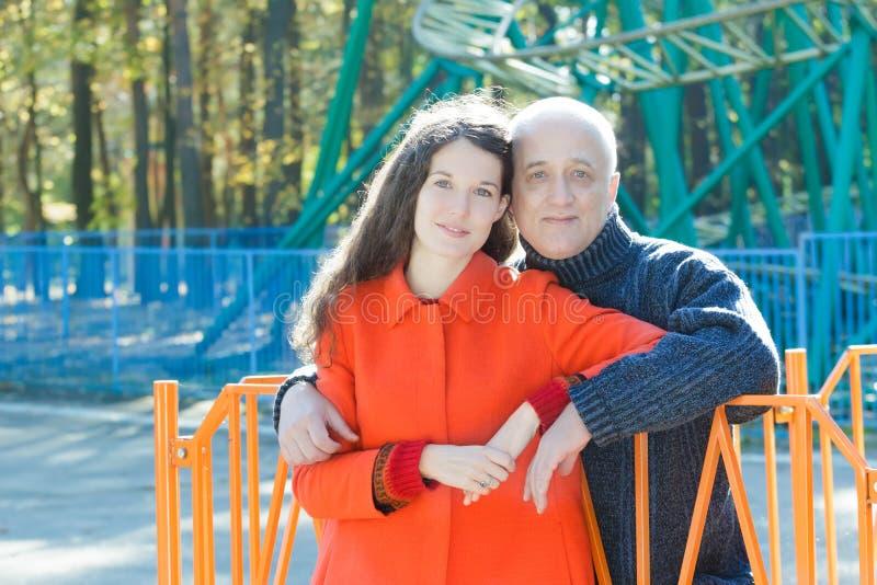 Retrato exterior de abraçar a filha adulta e seu pai superior no fundo do parque de diversões da montanha russa imagem de stock